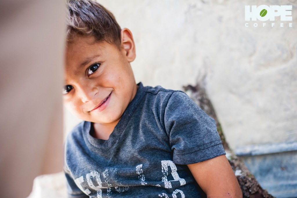 A playful 3-year-old boy smiles and hides behind his mom as she talks about the many needs her family faces. His family needs a new roof on their mudbrick home.